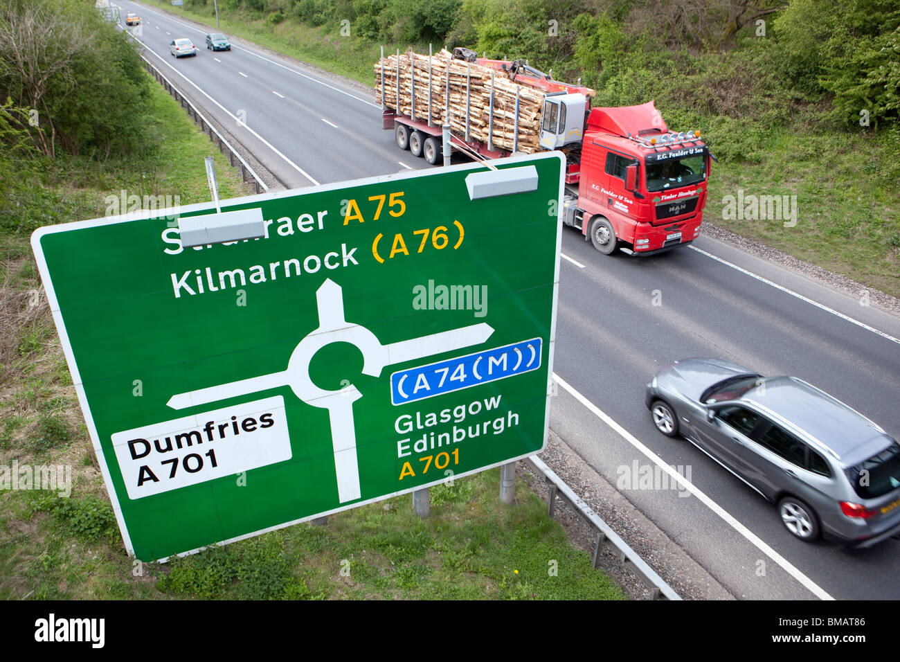 Road sign giving directions at roundabout on the A75 near Dumfries with cars and lorries speeding past UK - Stock Image