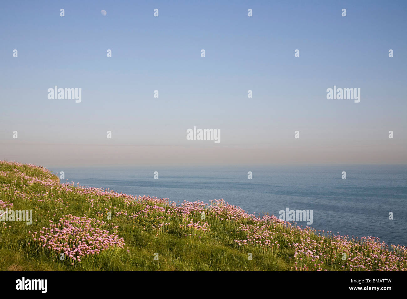 The English Channel off the Sussex Coast. The moon can be see in the East as the sun begins to set. - Stock Image