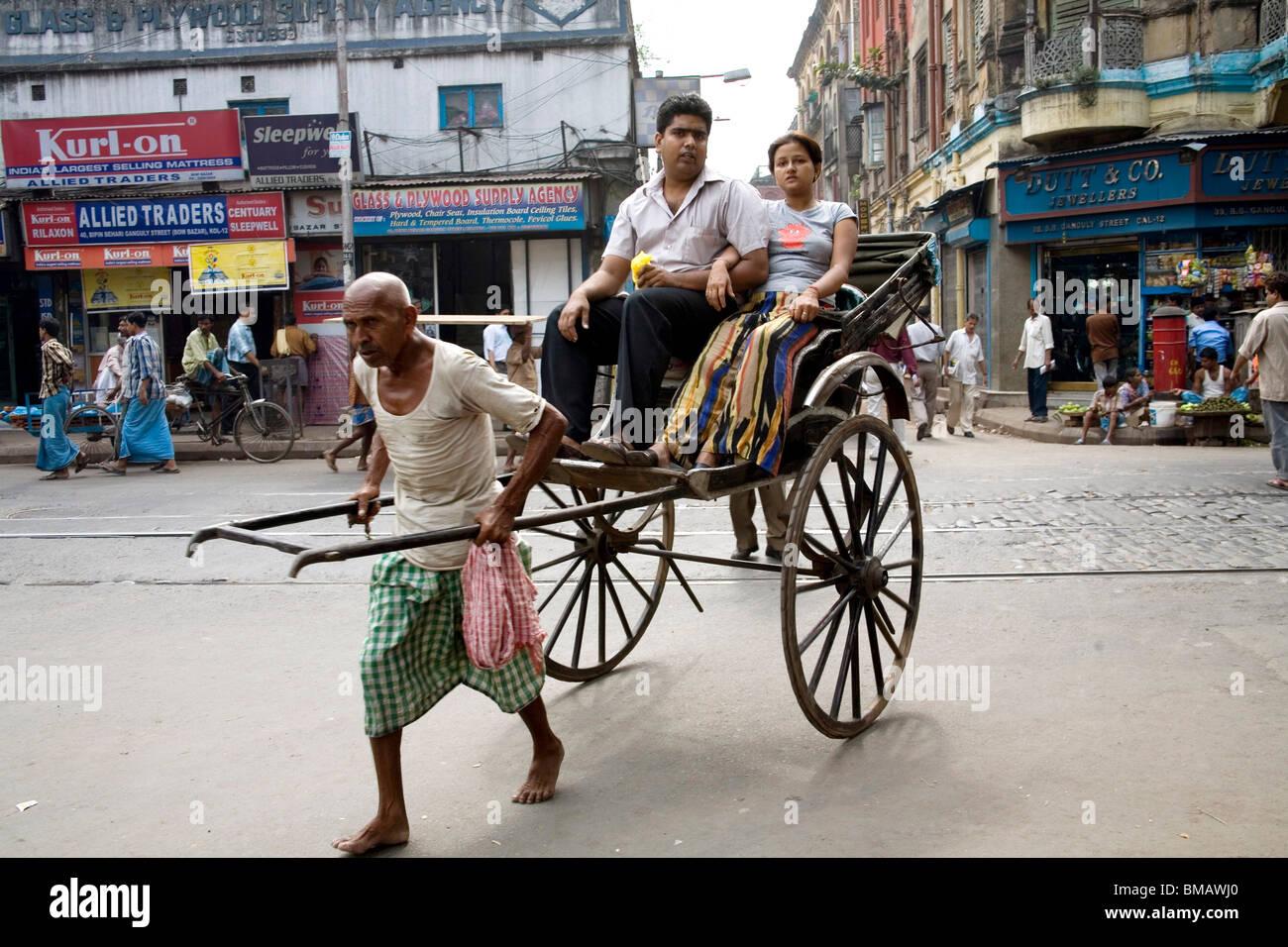 Manual labor ; man pulling hand rickshaw with passengers ; Calcutta now Kolkata ; West Bengal ; India - Stock Image