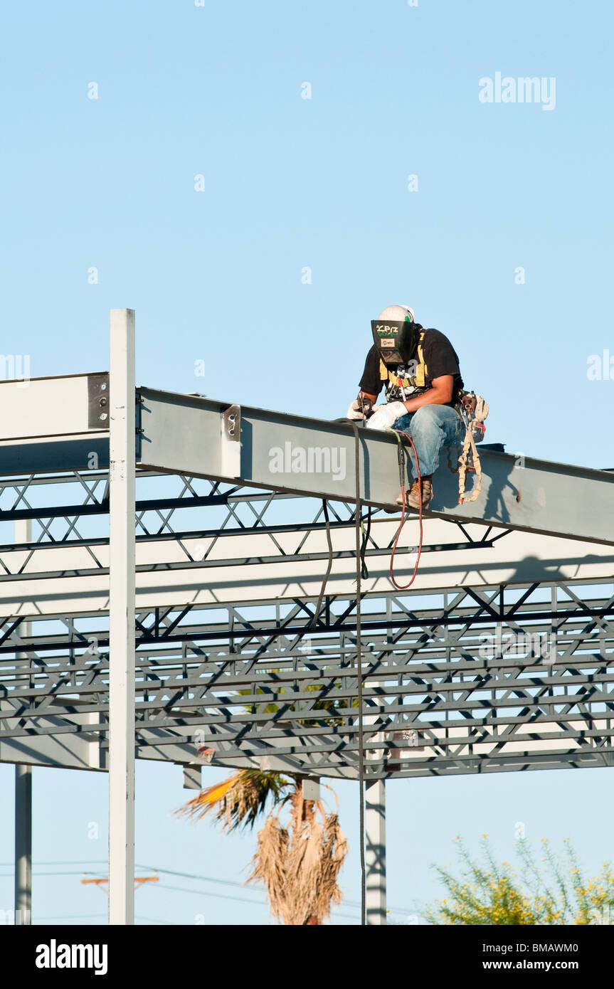 steelworker welds the structural steel framework for a commercial building - Stock Image