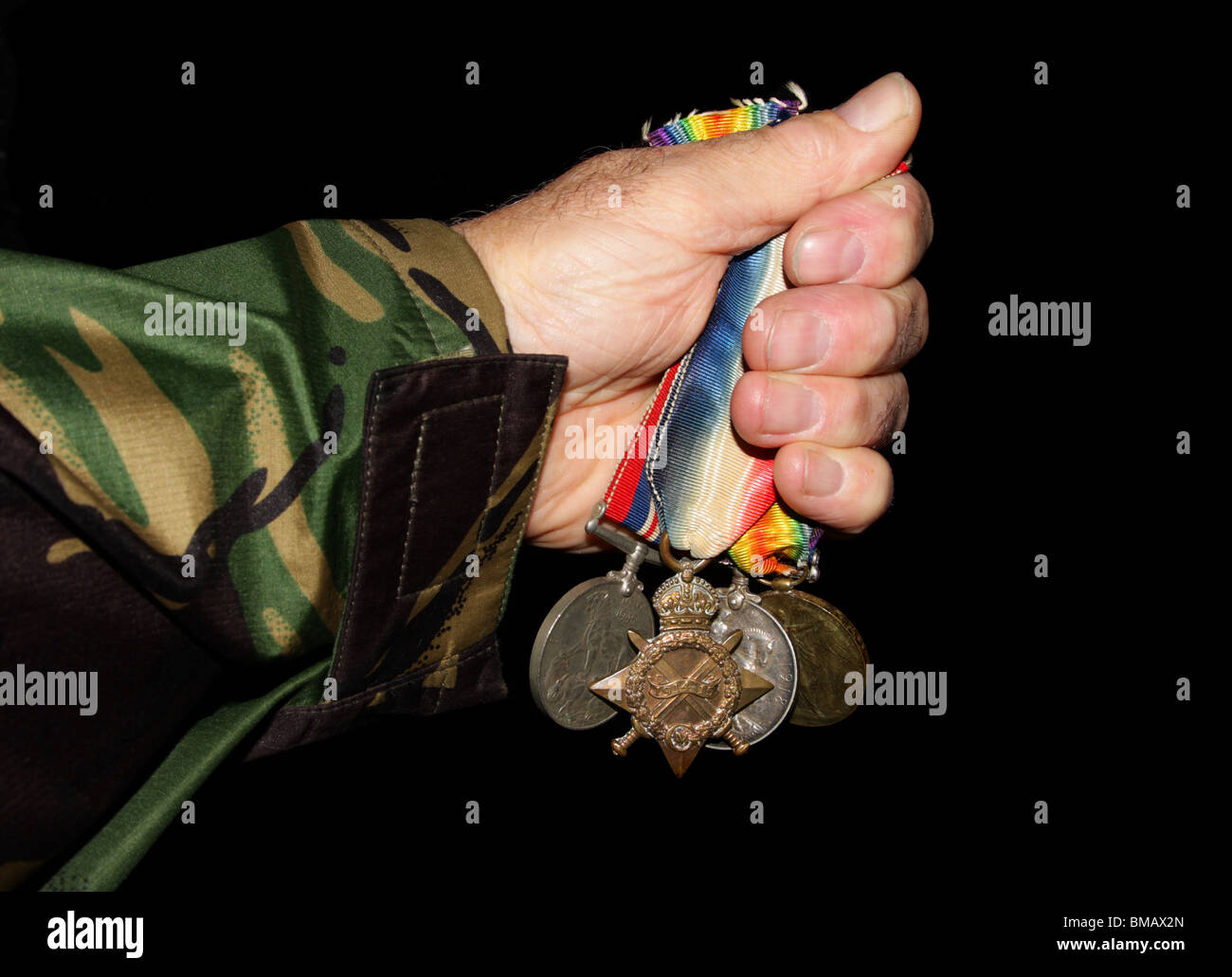 Collection of medals grasped in a soldiers hand. - Stock Image