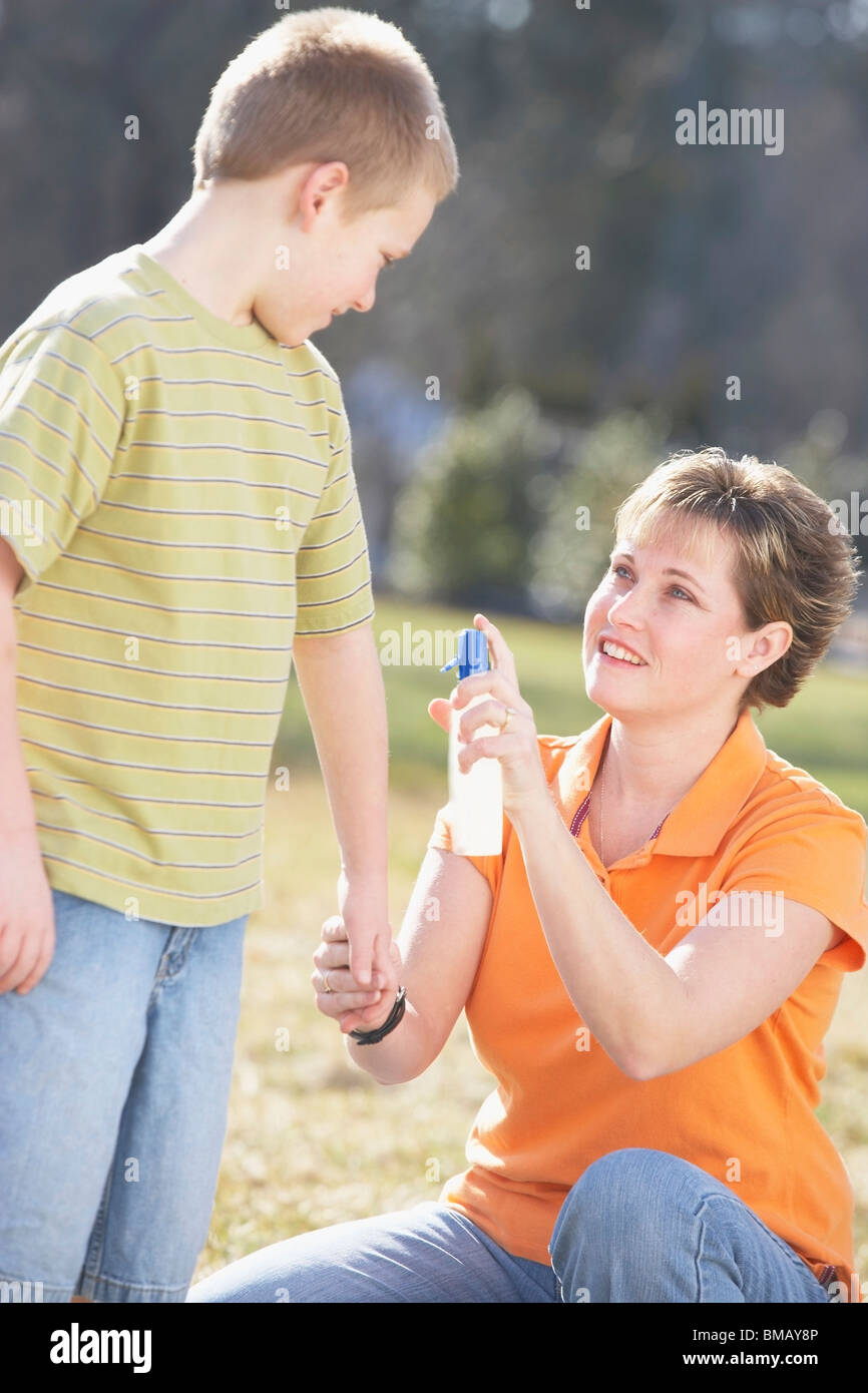 A Mother Spraying Insect Repellent On Her Son - Stock Image
