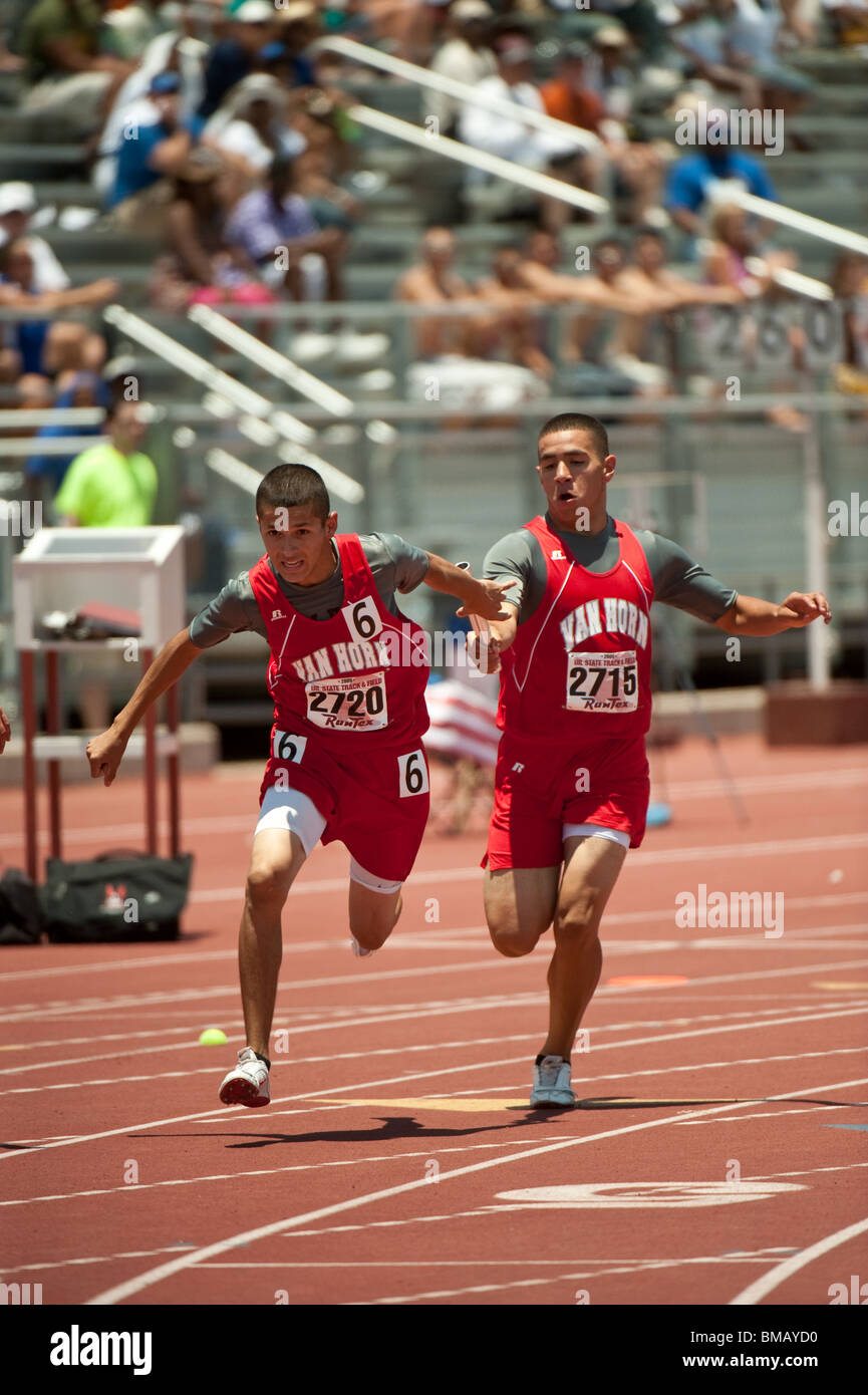 Male runner hands off baton to teammate  during relay race at the Texas high school state championship track meet - Stock Image