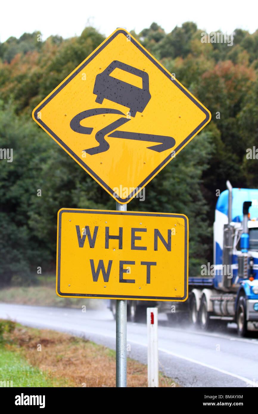 Australian yellow sign indicating slippery when wet - Stock Image