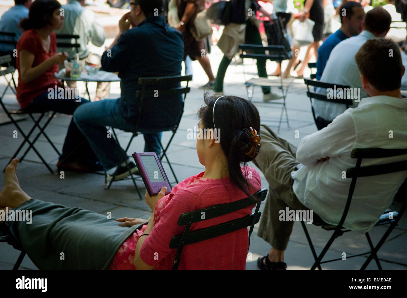 A reader uses her Sony Reader electronic book in Bryant Park in Midtown Manhattan in New York - Stock Image