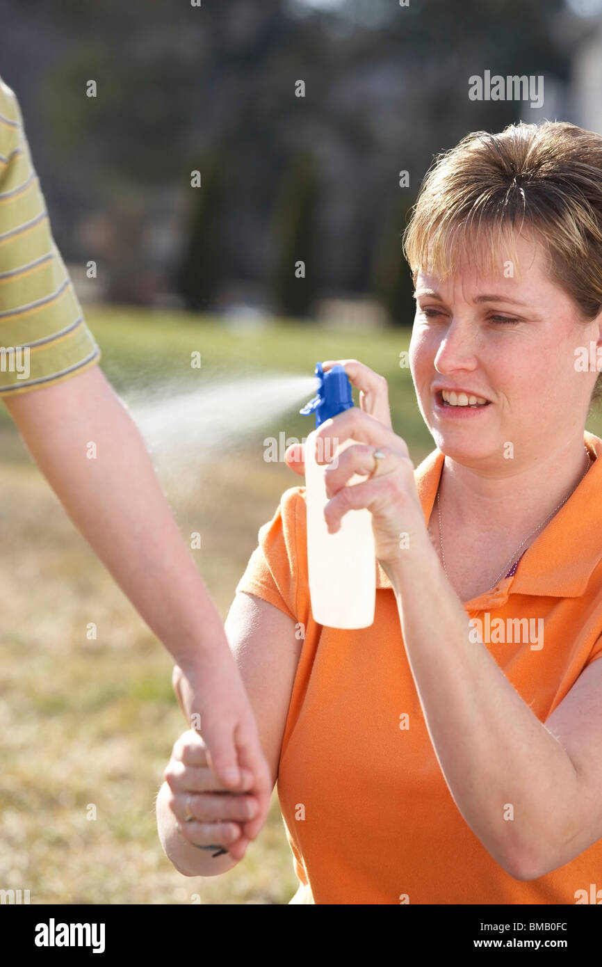 A Mother Spraying Insect Repellent On A Child's Arm - Stock Image