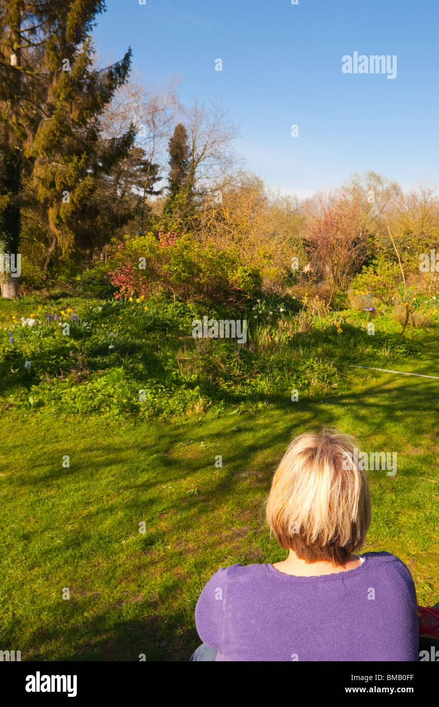 A MODEL RELEASED picture of a woman in her 30's in a cottage garden in Suffolk , England , Great Britain , Uk - Stock Image