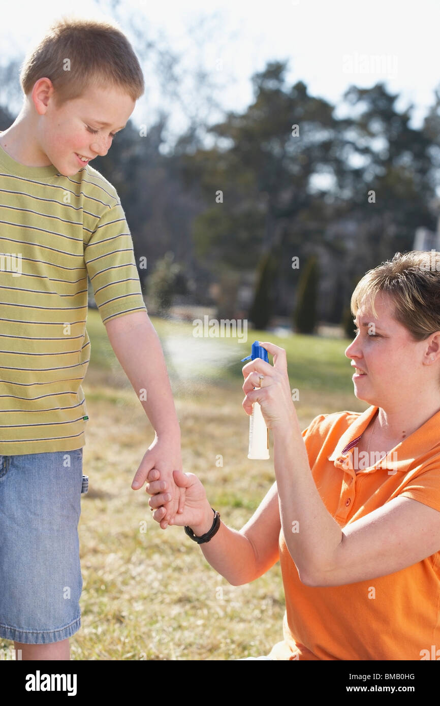 A Mother Spraying Insect Repellent On Her Son's Arm - Stock Image