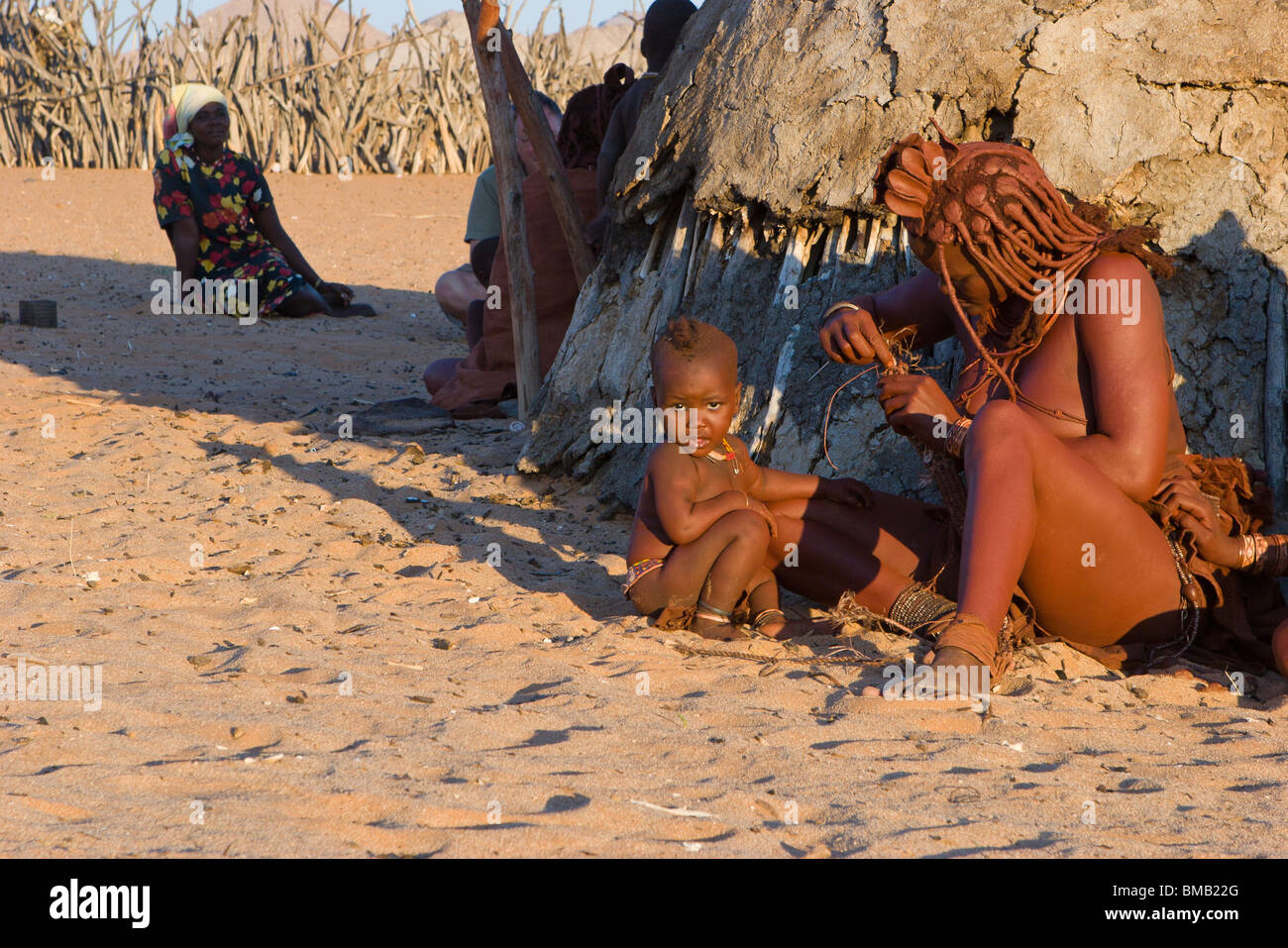 Nomadic Himba Tribe, Mother and Child weaving in warm evening sunlight by cow dung hut dressed in traditional costume - Stock Image