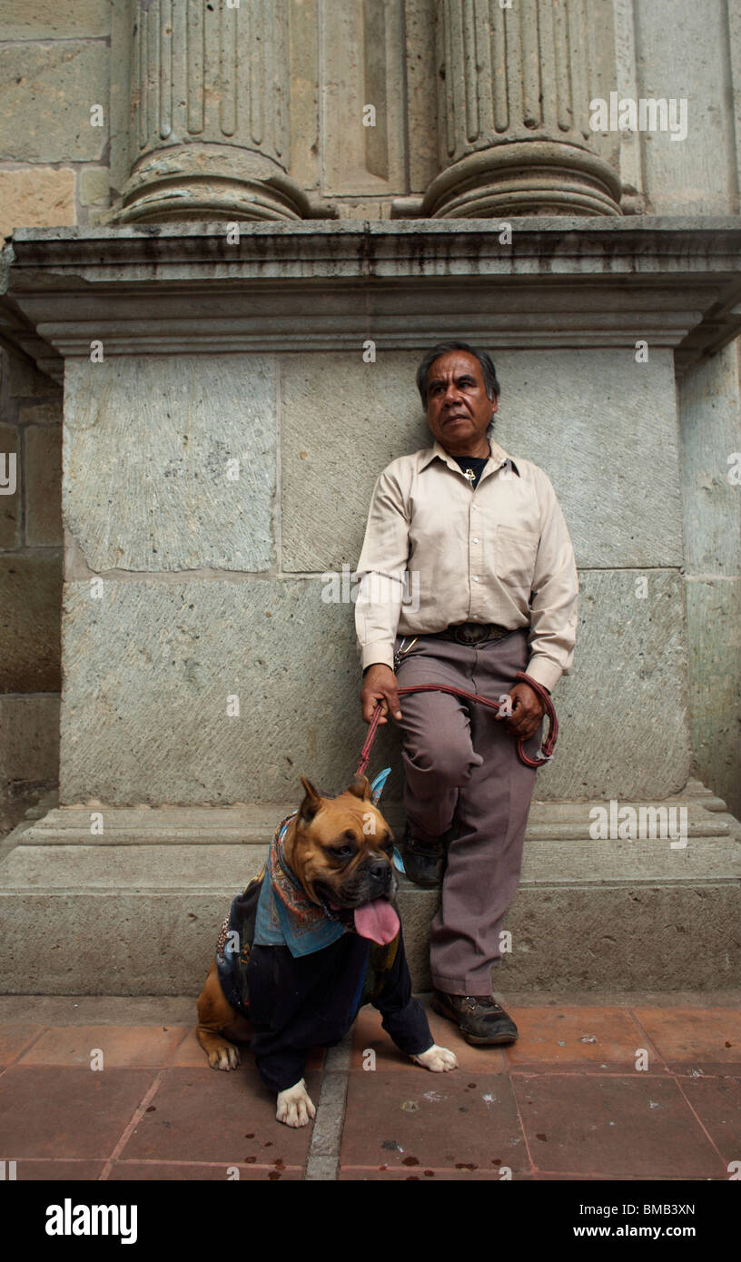 A man stands with his dog at La Merced Catholic church during the Blessing of the Animals celebration in Oaxaca, - Stock Image