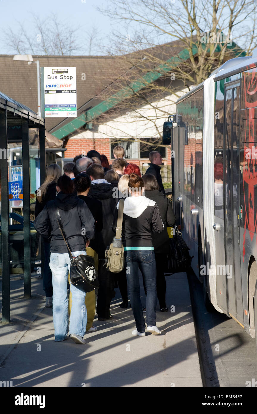 Passengers boarding a bus at a bus stop in England - Stock Image