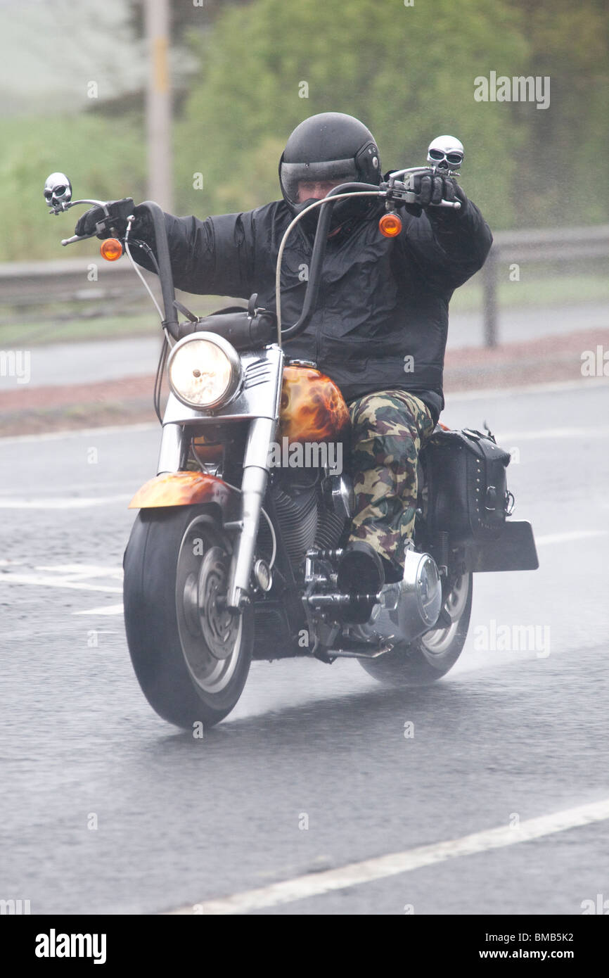 Dual carriageway road A75 UK bad weather rain mist spray a wet motorcyclist on a chopper motorbike heading the North - Stock Image