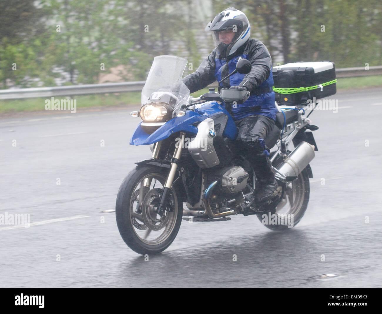 Bad weather rain mist spray dark road touring motorbike with a wet motorcyclist summer UK - Stock Image