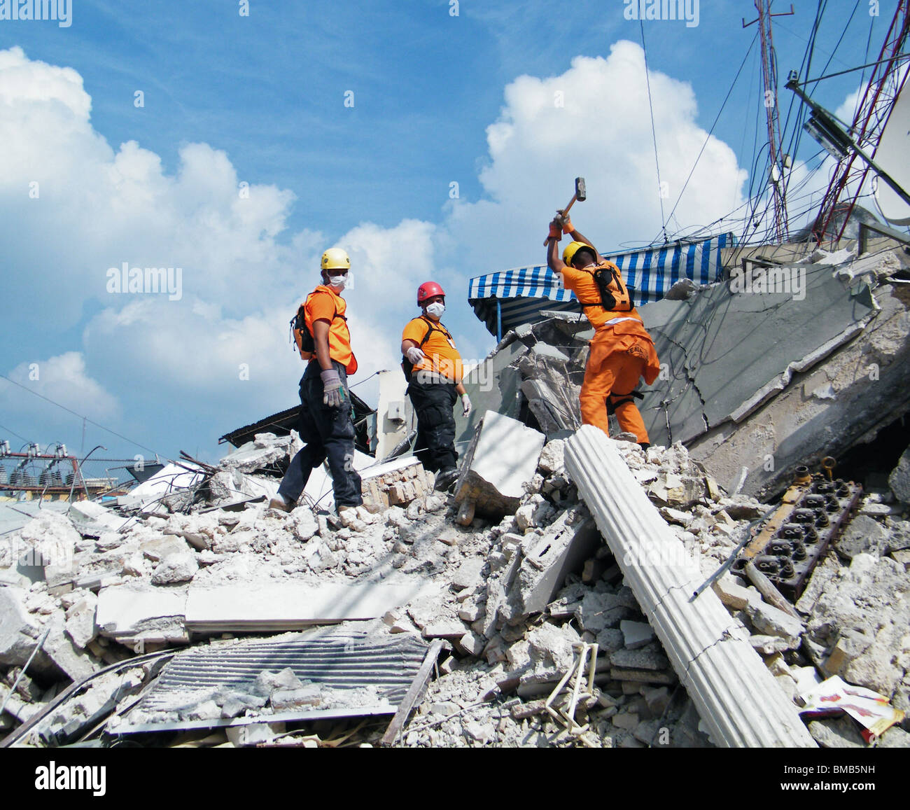 Dominican rescuers from the Defensa Civil search for survivors under the rubble in Port au Prince after the Haiti - Stock Image