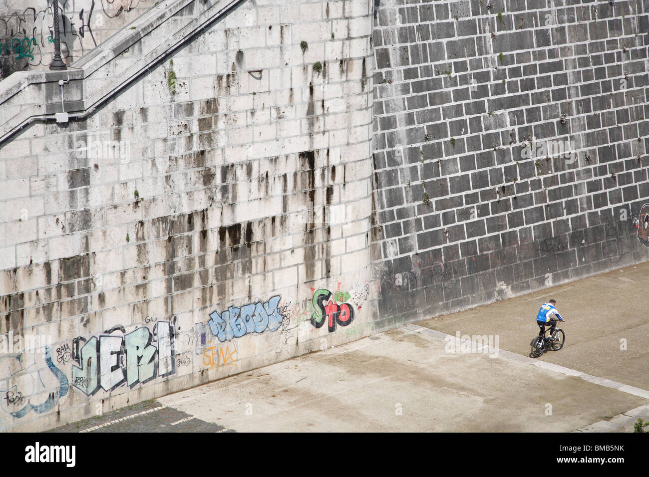 Bicyclist, Graffiti, river embankment, Rome, Italy - Stock Image