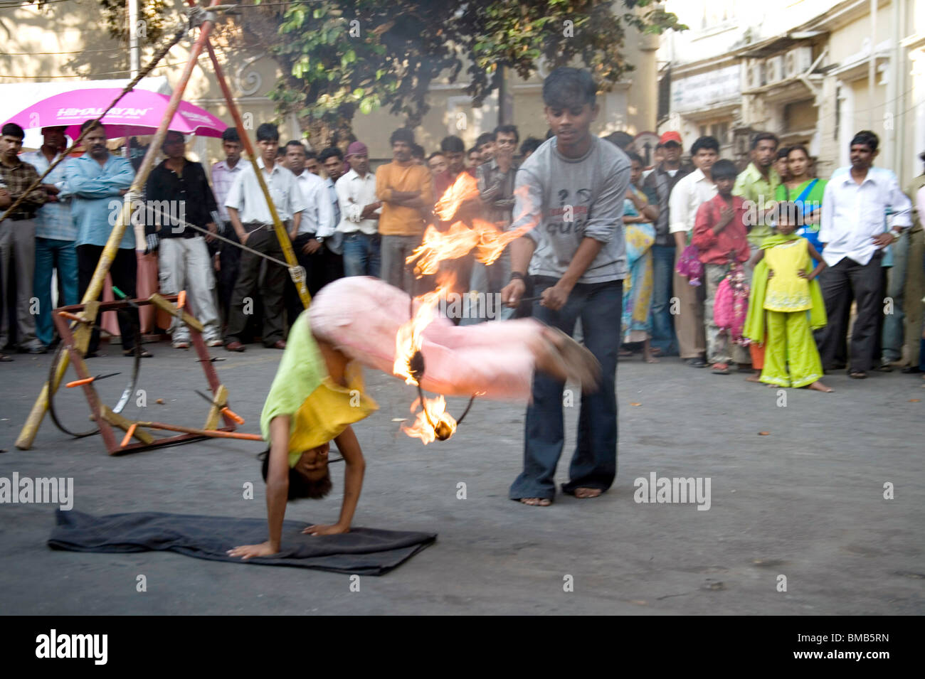 Boy jumping through iron ring, fire performance in Kala ghoda festival art fair ; Bombay Mumbai ; Maharashtra ; - Stock Image
