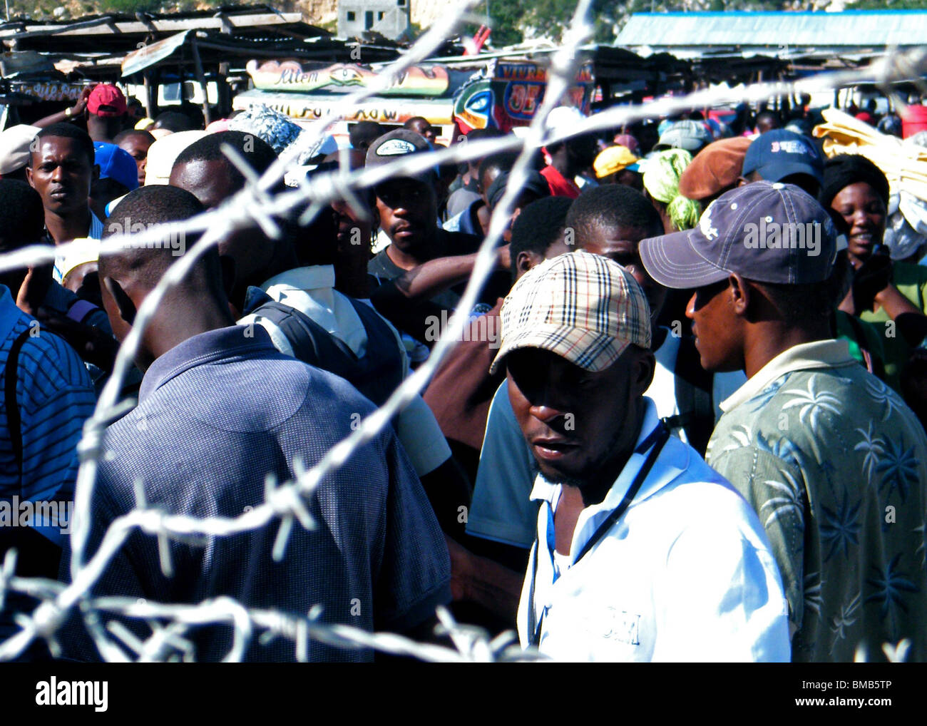 Haitians crowd the gates at the Dominican Republic border (Jimani - Malpasse) after the Haiti earthquake - Stock Image