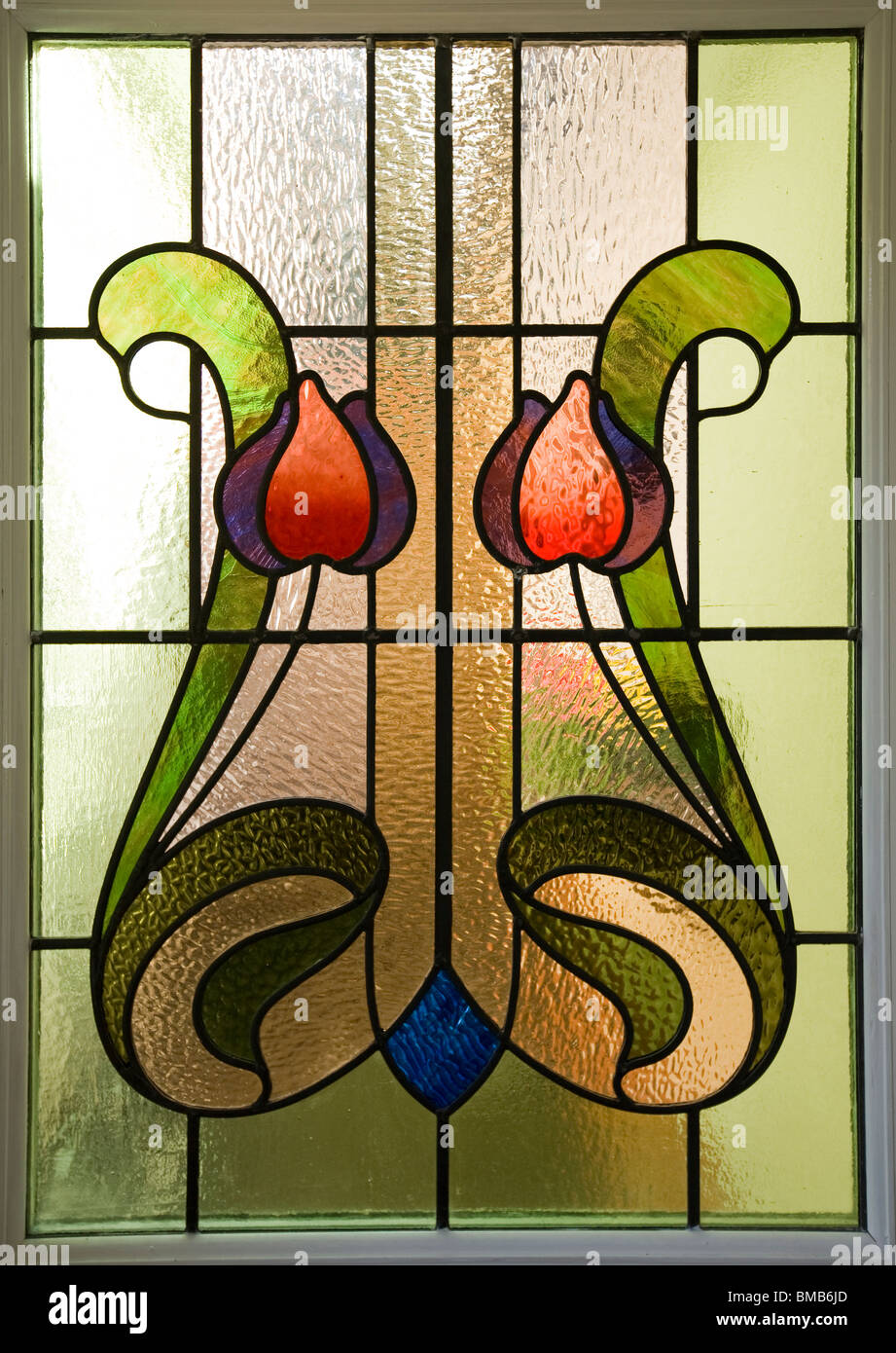 Houses Edwardian arts and crafts house, colourful art nouveau stained glass window panel - Stock Image