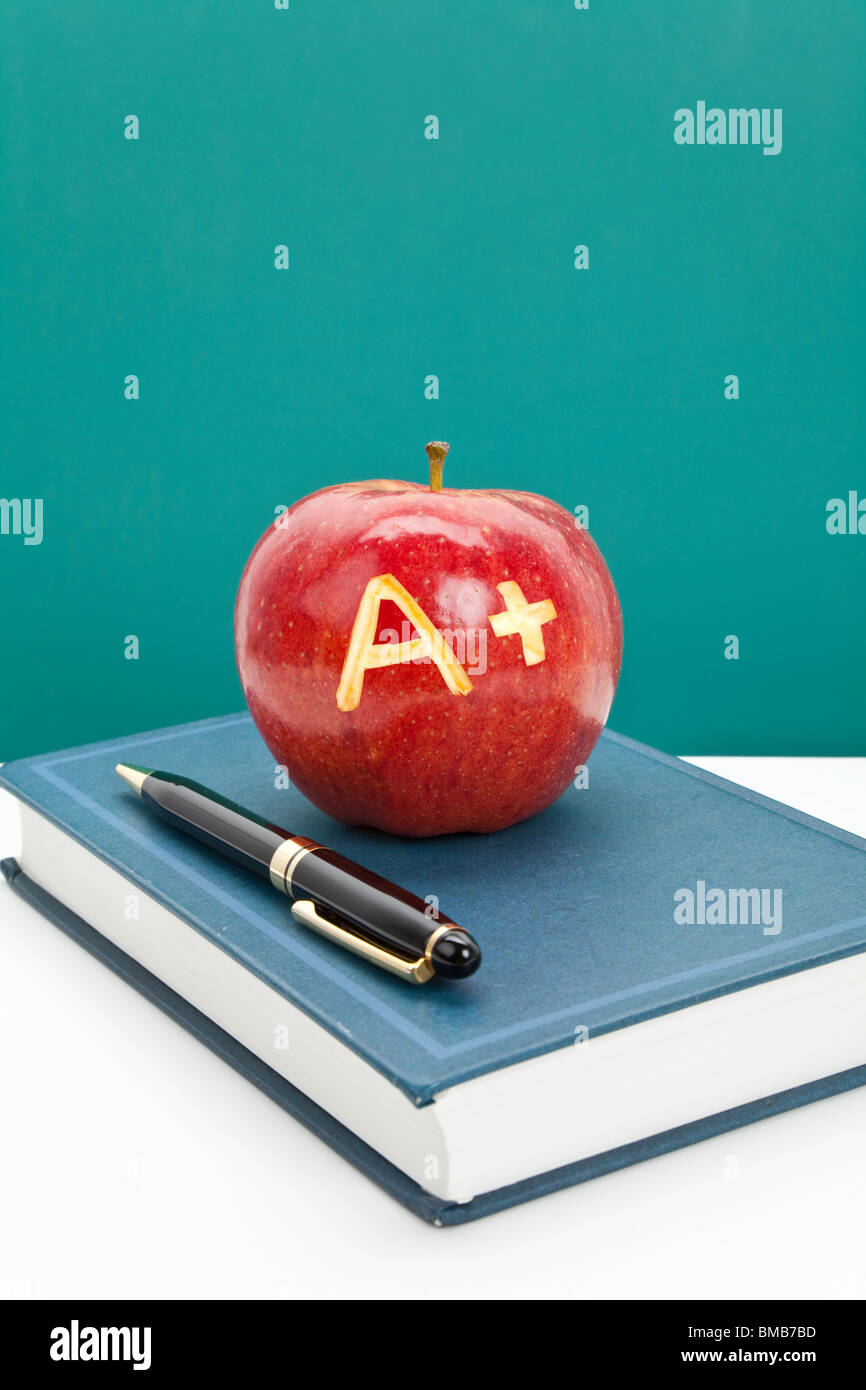 Red apple and Textbook close up - Stock Image