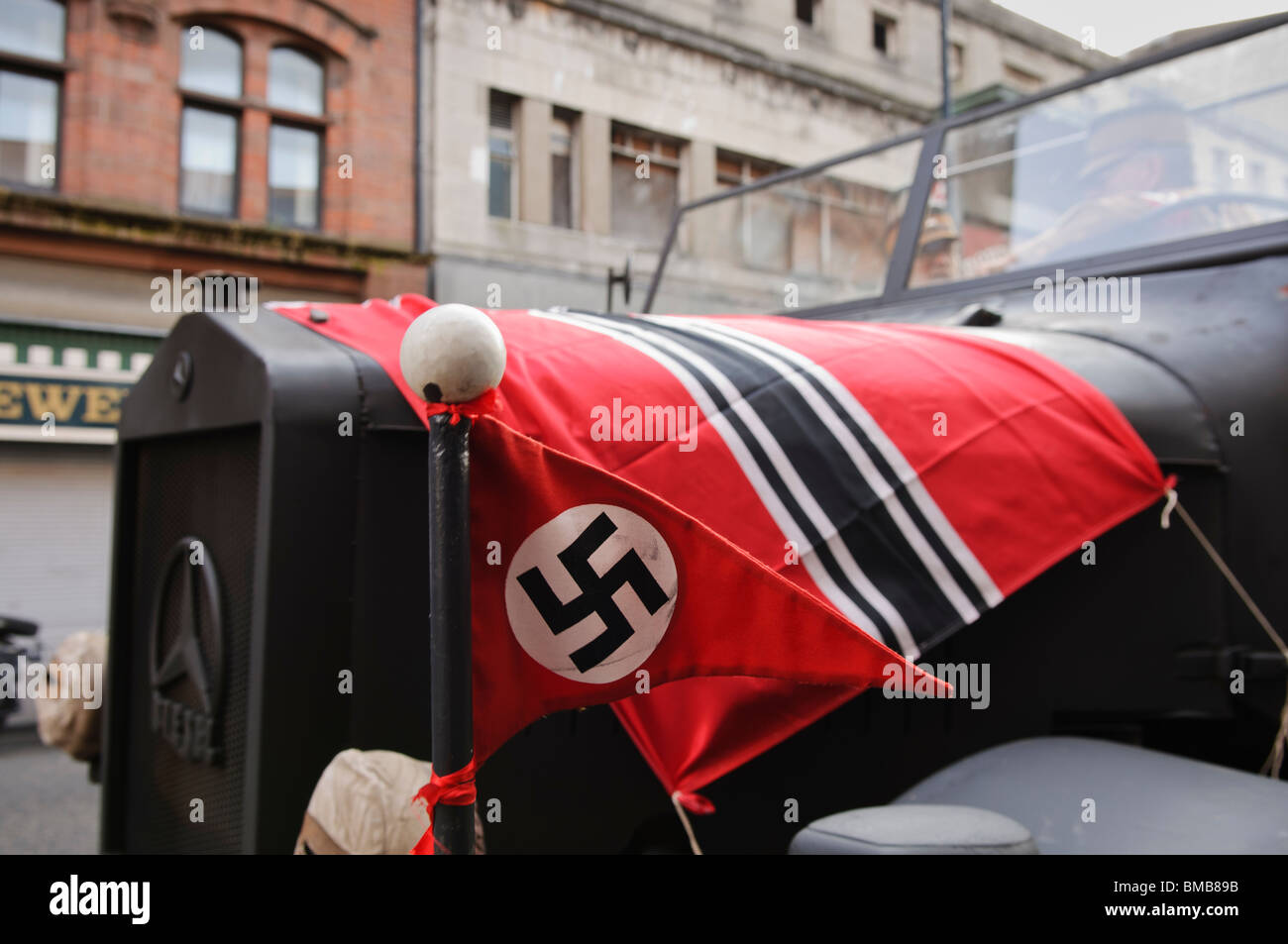 Nazi flags on the bonnet of a German Army truck during the shooting of a film set in 1930s Berlin. - Stock Image