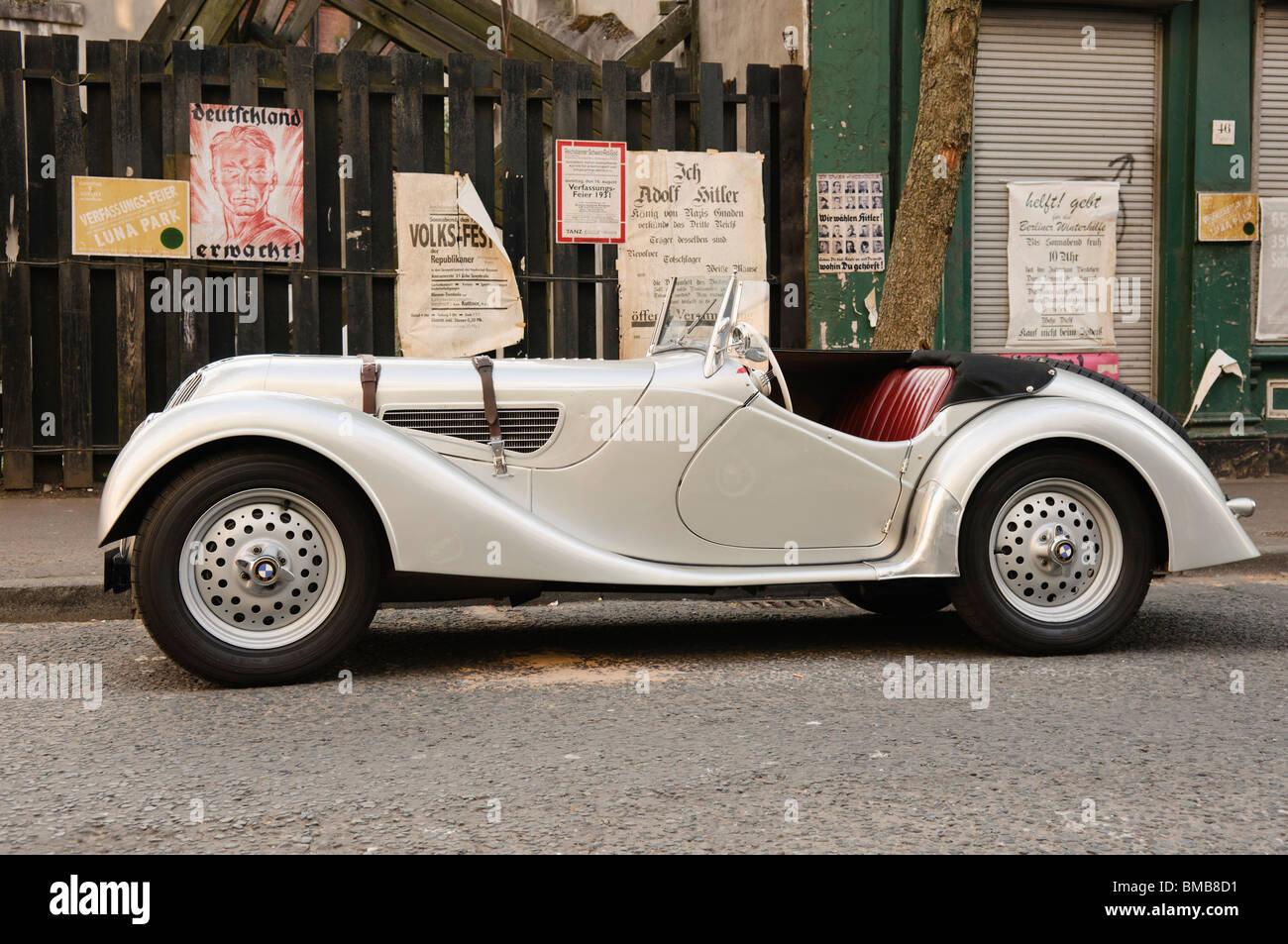 BMW 328 roadster from the latter half of the 1930s on a film set recreating Berlin in the mid 1930s with Nazi propaganda - Stock Image