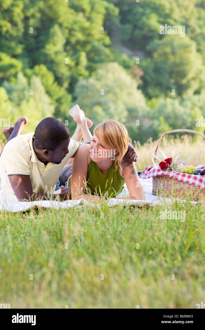 portrait of young multiethnic couple picnicking in park - Stock Image