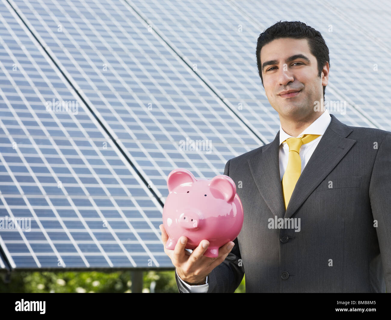 engineer holding piggy bank and standing near solar power station - Stock Image