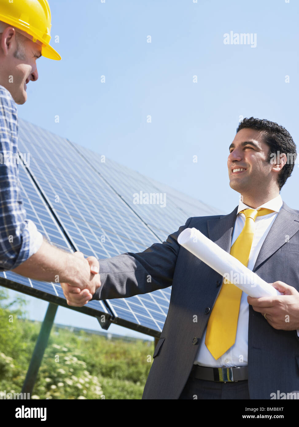 engineer and manual worker shaking hands near solar panels - Stock Image