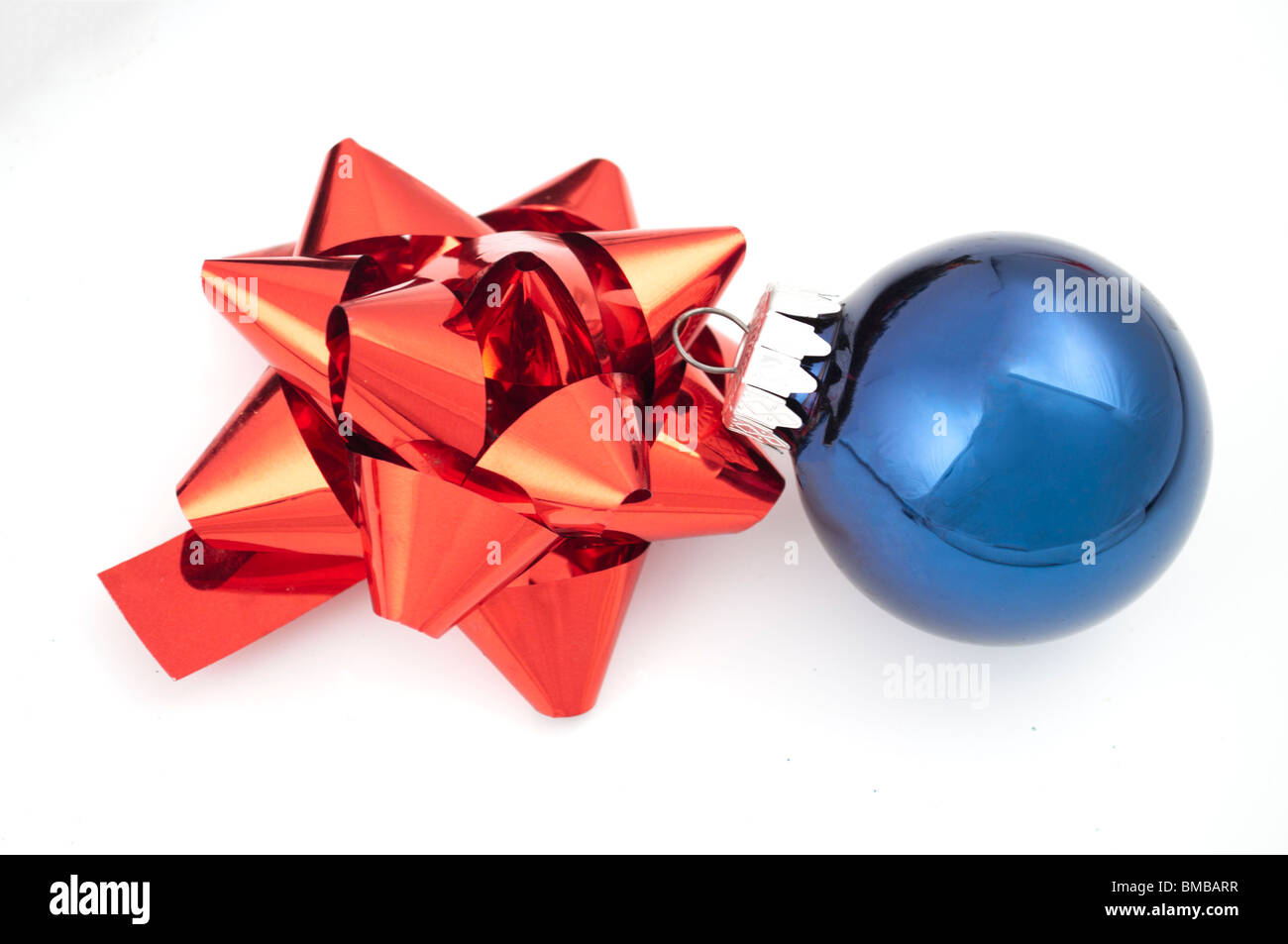 Red bow and blue christmas ball on white - Stock Image