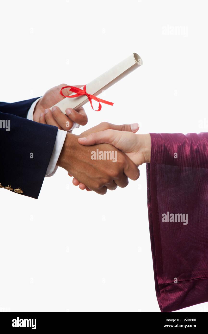 handshake and a diploma at graduation - Stock Image