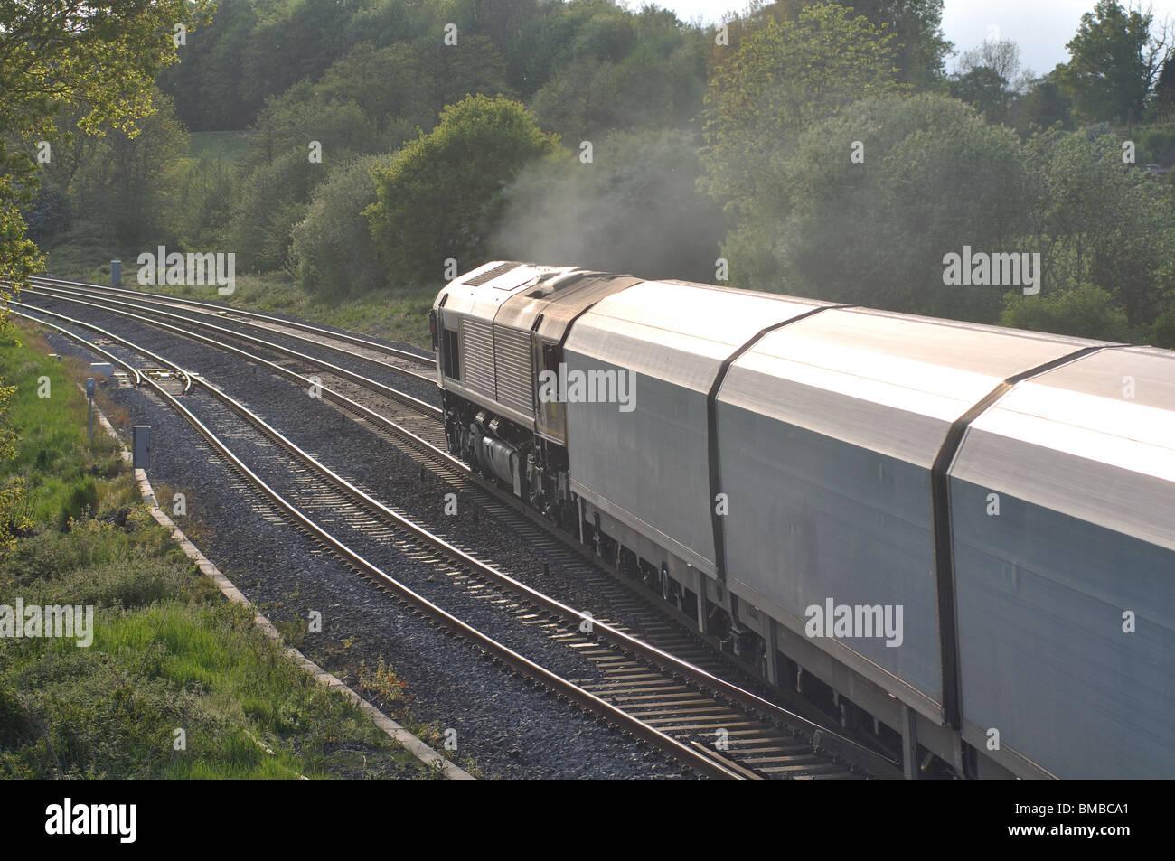 Diesel locomotive pulling covered car transporter wagons, UK - Stock Image