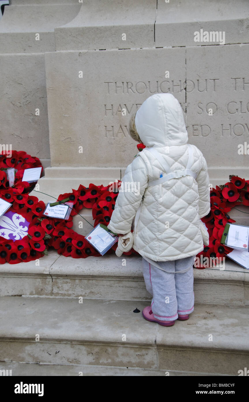 Young girl looks at poppy wreaths during Remembrance Sunday - Stock Image