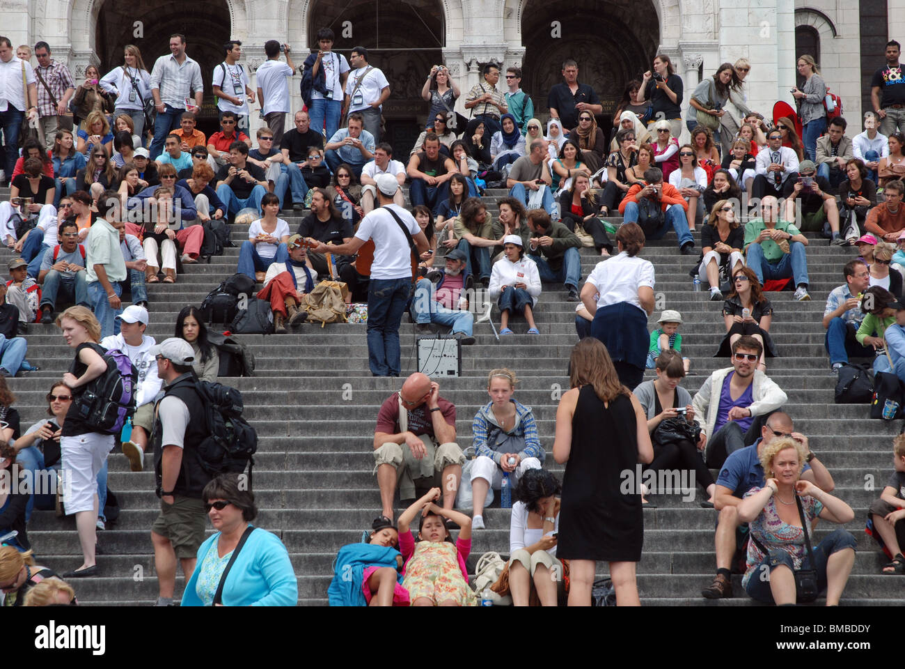 Tourists on the steps in front of  the Sacré-Coeur Basilica church. Montmartre, Paris. - Stock Image