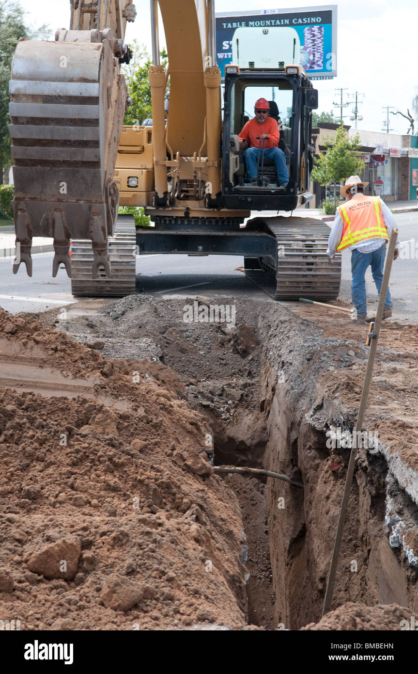 digging a trench on a street in town - Stock Image