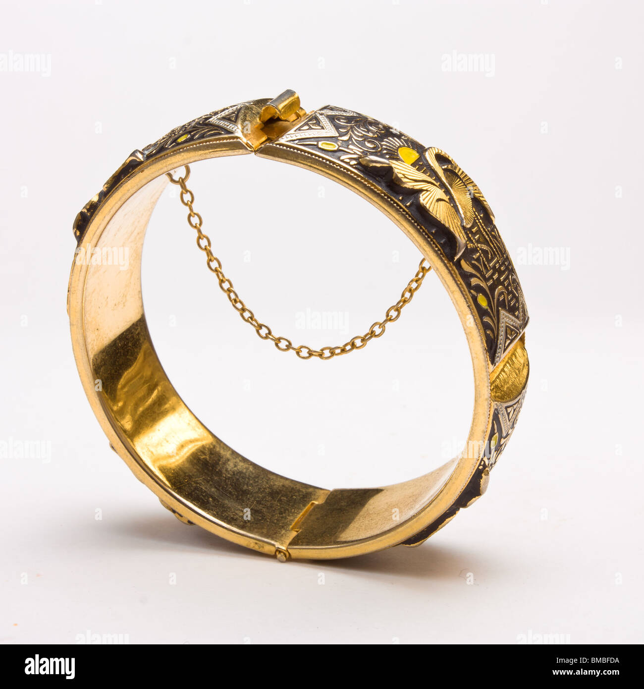 Gold bangle with safety chain isolated against white background - Stock Image