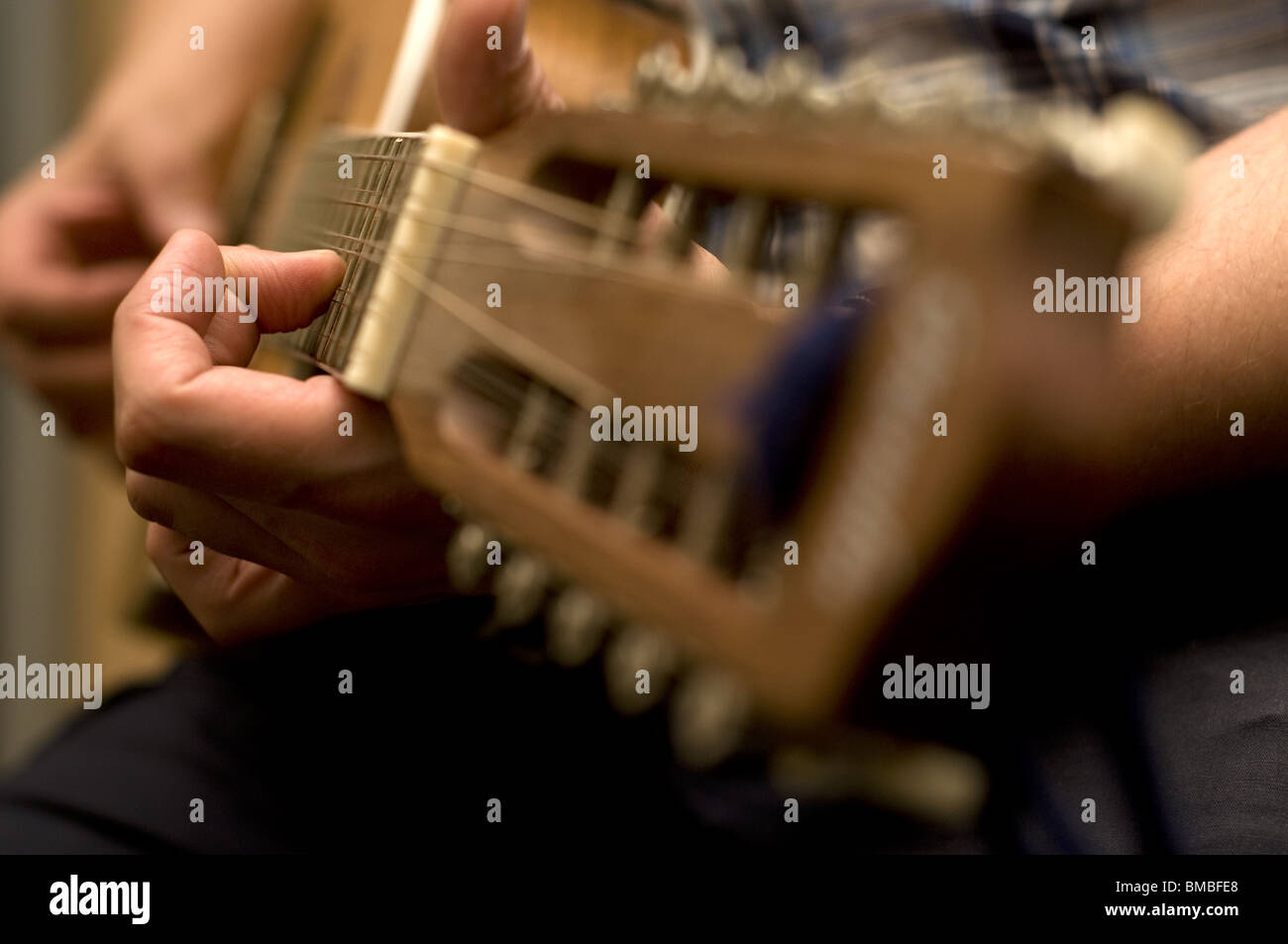 Man Playing a classical guitar. Shows fretboard and crop of hands playing notes. - Stock Image