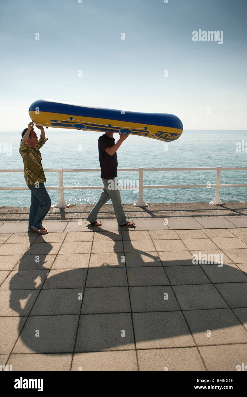 Two young men students carrying an inflated dinghy to Aberystwyth beach, Cardigan Bay, West Wales, summer afternoon, - Stock Image