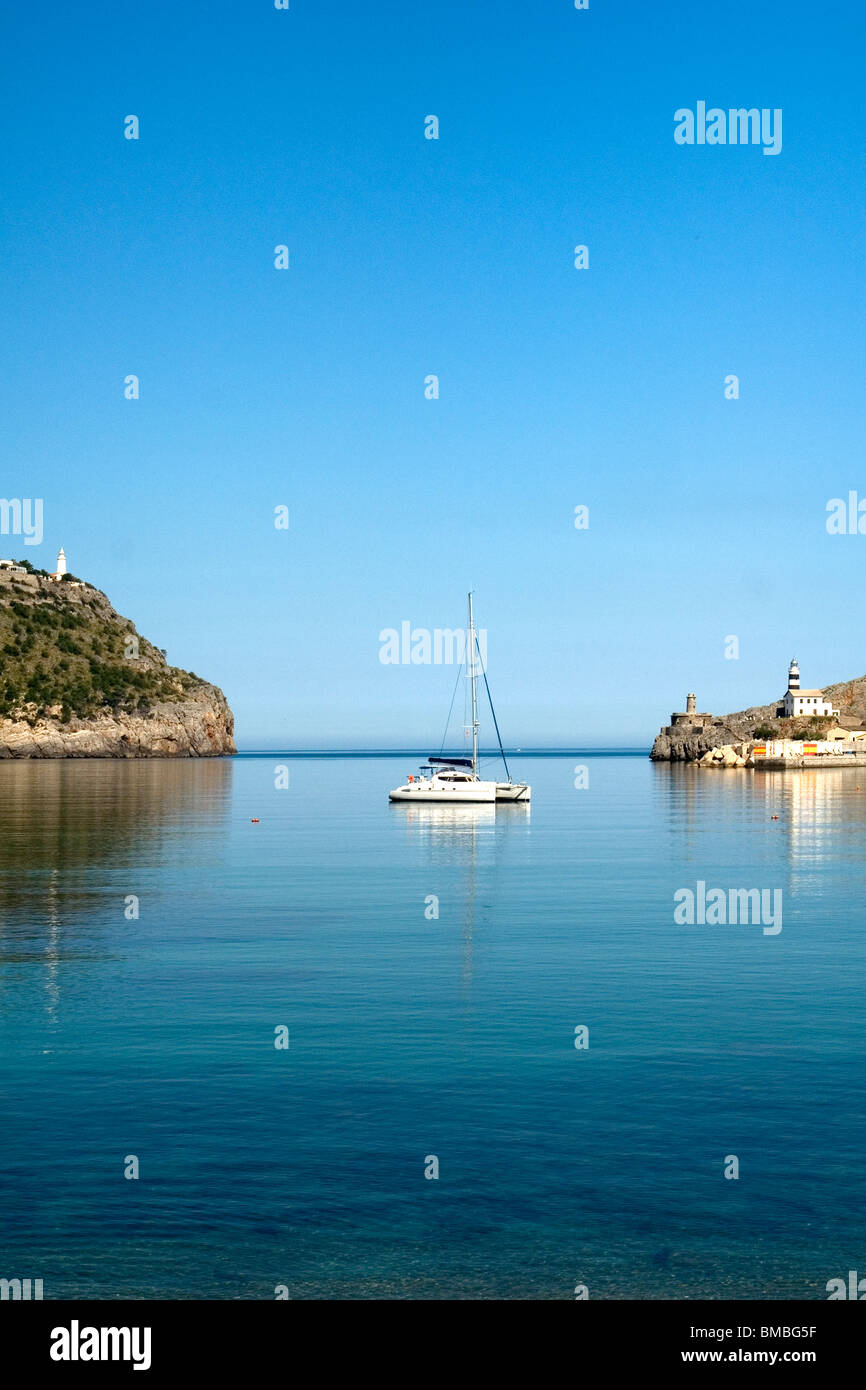 By dead calm, a symmetrical view of a sailing boat in relation to the entry of the Port de Soller (Majorca - Spain). - Stock Image