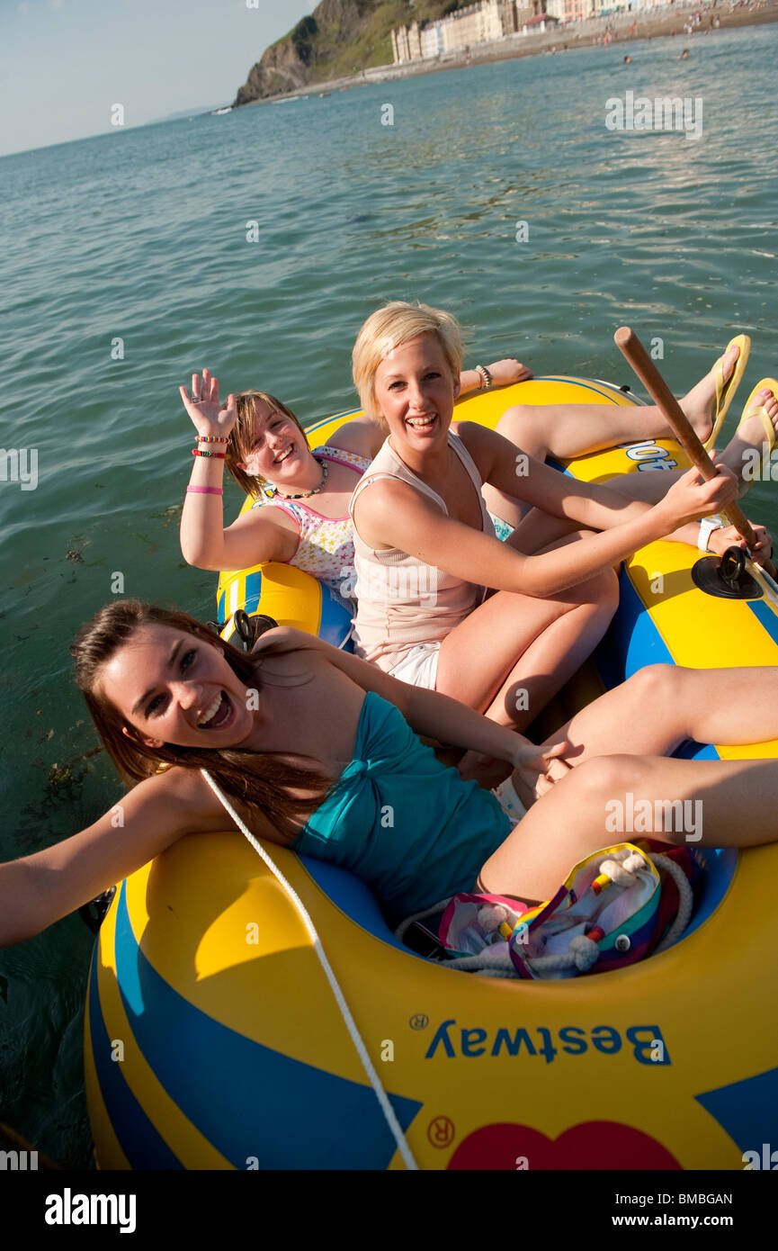Three young women students in an inflatable dinghy off Aberystwyth beach, Cardigan Bay, West Wales, - Stock Image
