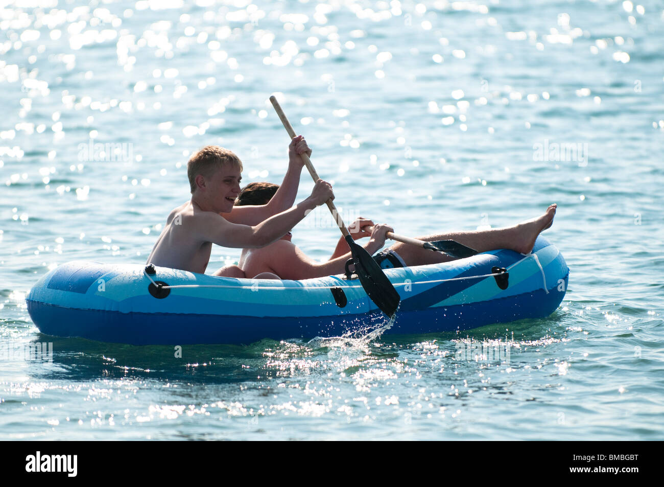 Two young students rowing an inflatable raft dinghy in the sea, Aberystwyth Wales UK - Stock Image