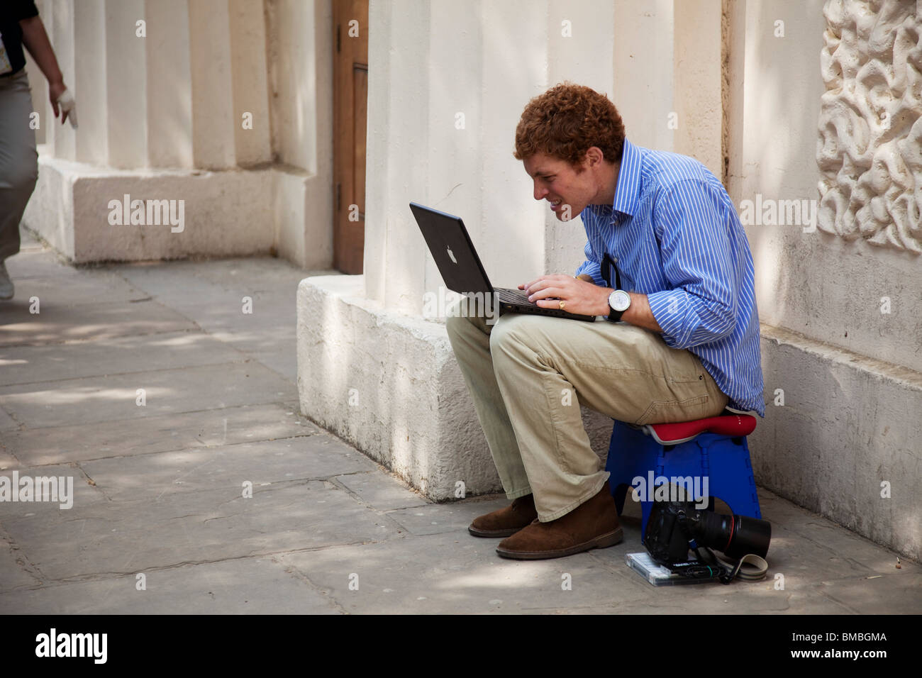 A photographer busily prepares his files on his Mac laptop to swiftly wire to his newspaper or wire service. - Stock Image
