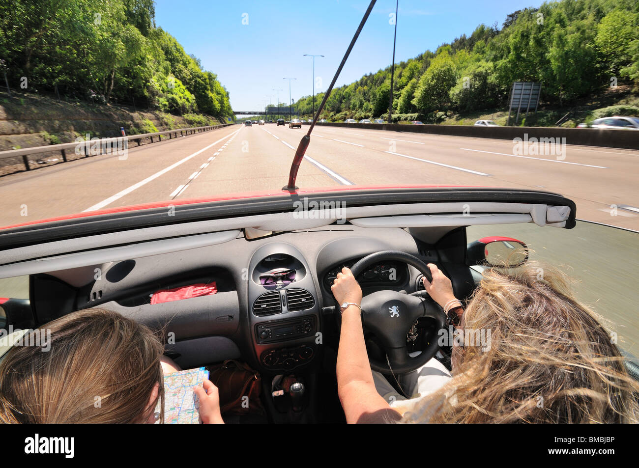 Open top car with female driver and passenger on open road Stock Photo