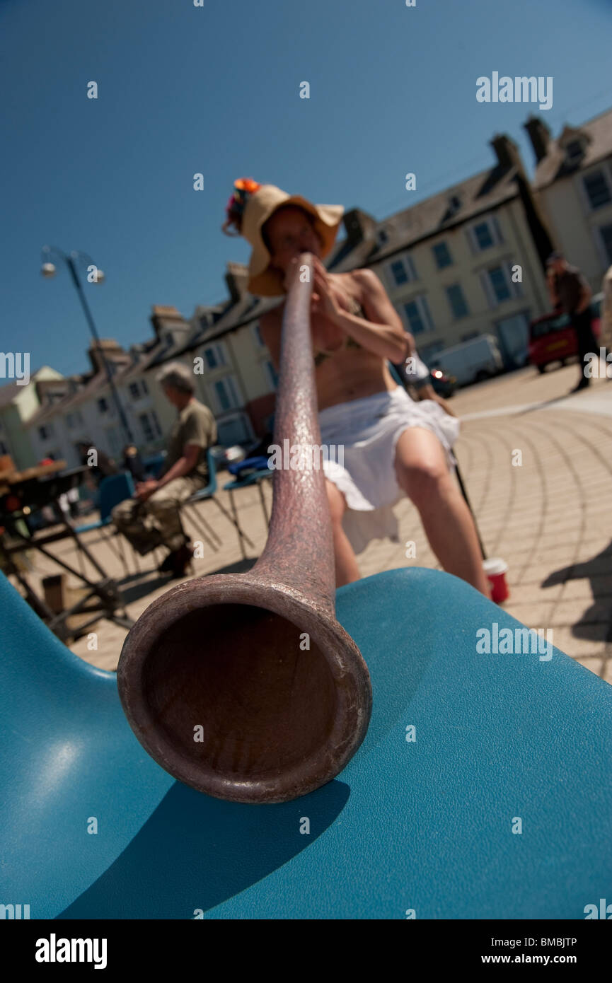 A young woman playing the didgeridoo on Aberystwyth promenade on a hot summer day, Wales UK - Stock Image