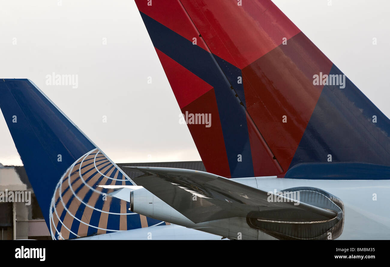 Delta Airlines and Continental Airlines logos on the tail section of two of their respective company's passenger - Stock Image