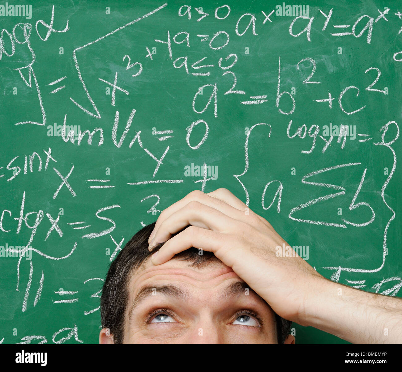 Confused Man in Front of Math Formula Written on a Chalkboard - Stock Image