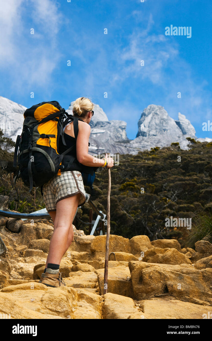 Hiker on Mt Kinabalu trail with the mountain peak in the background. Kinabalu National Park, Sabah, Borneo, Malaysia. - Stock Image