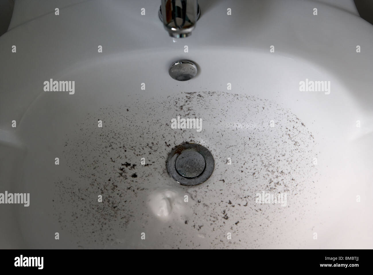 dirty bathroom sink with remnants of mans shaving after a weekends growth - Stock Image