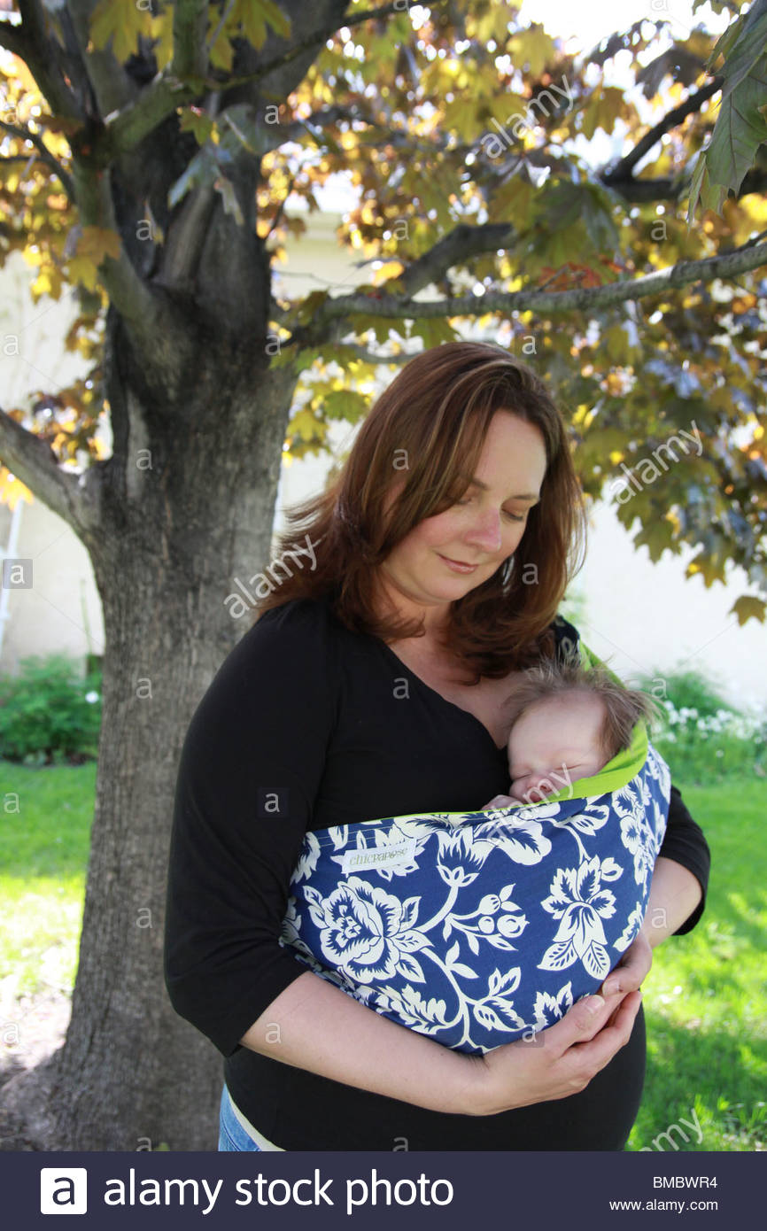 A mother holding her newborn baby in an infant sling. - Stock Image