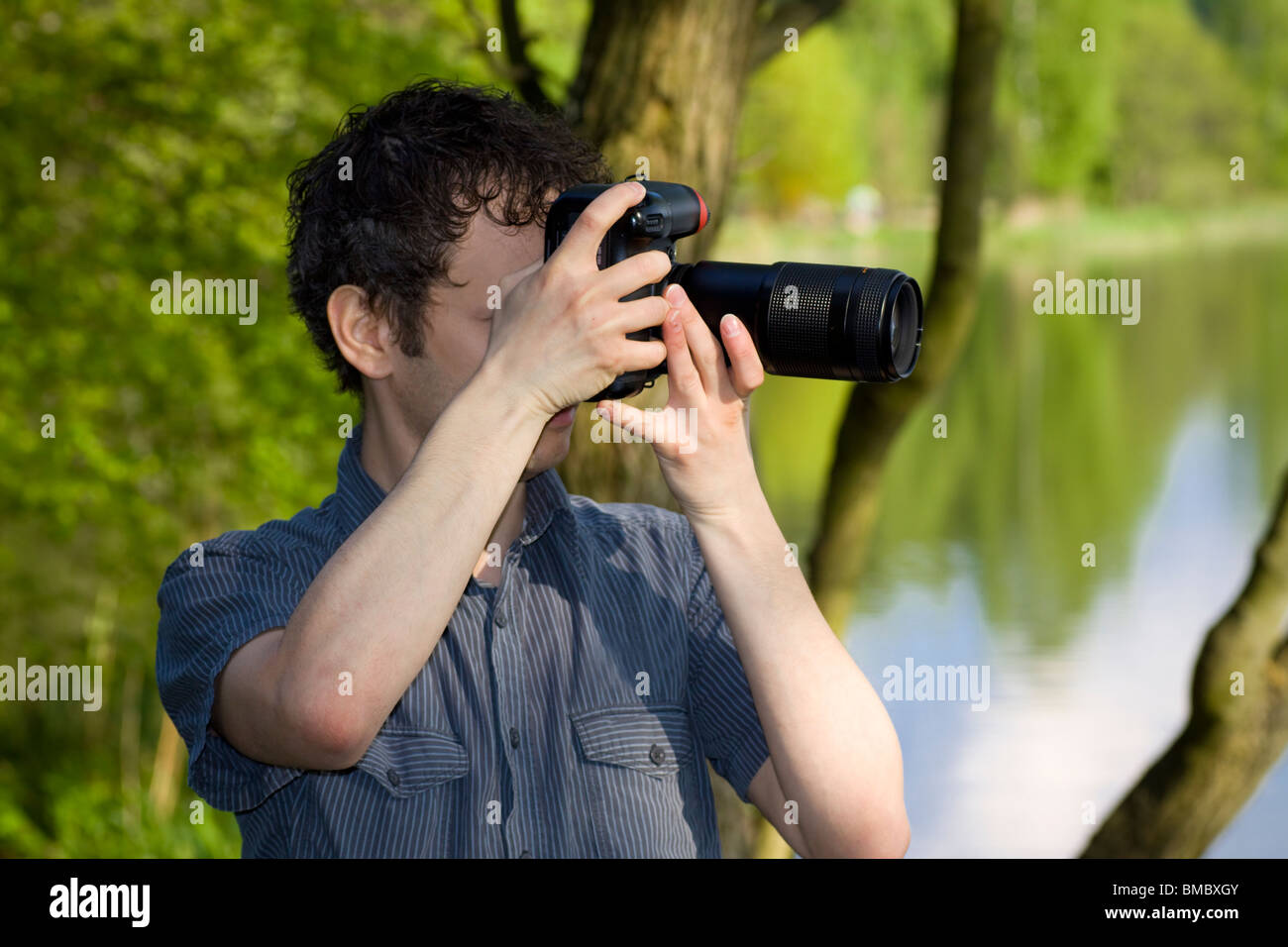 Sneaky photographer getting his shot of nature - Stock Image