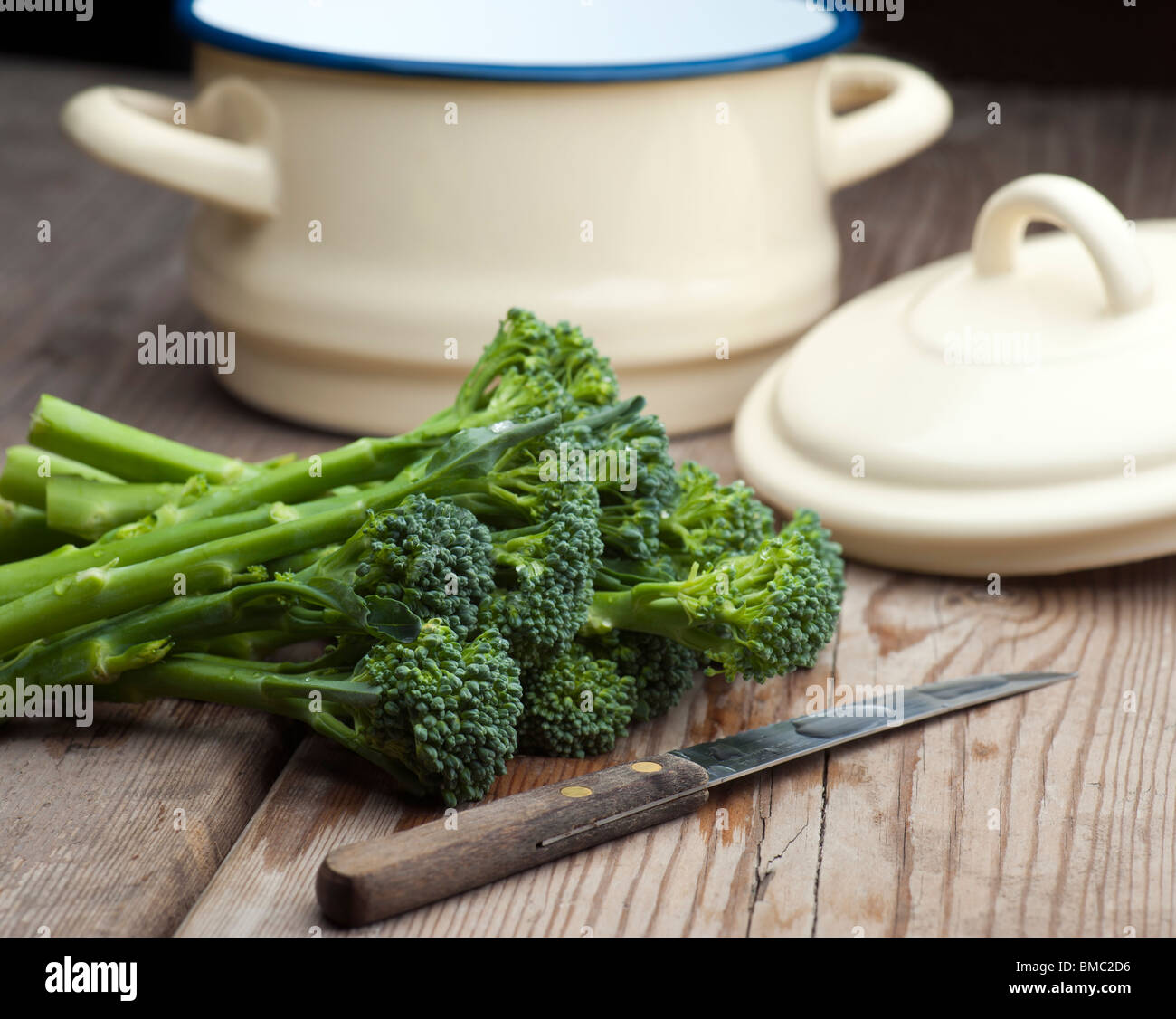 Fresh Broccoli Laid On A Wooden Kitchen Table With A Vegetable Knife and A Pan With Lid In The Background - Stock Image